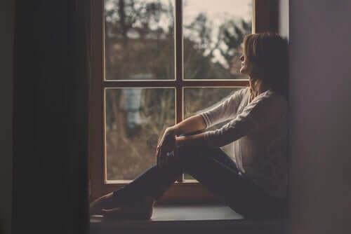 Mulher na janela pensando