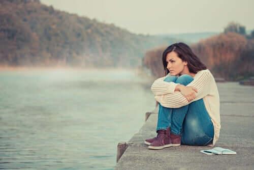 Mulher pensativa em lago