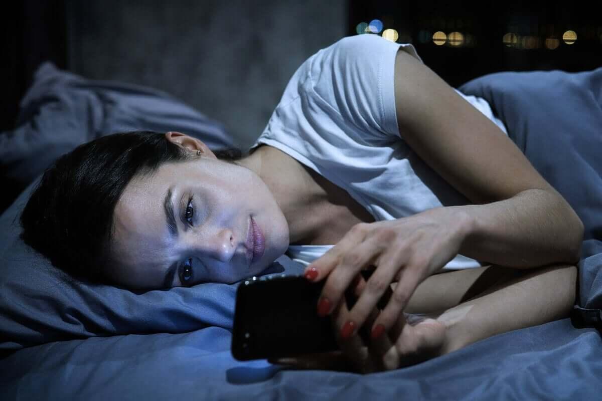 Mulher ao telefone antes de dormir