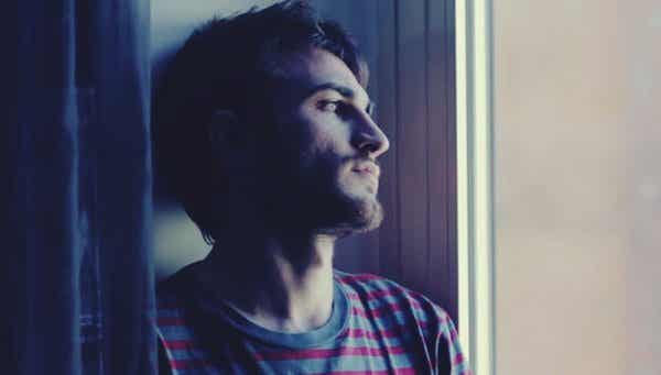 Rapaz triste olhando pela janela
